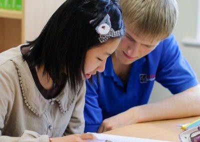 Британский студент-помощник участвует в выполнении домашнего задания в летнем лагере Etherton